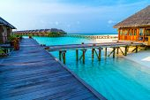 Water Villas, Bungalows And Wooden Bridge At Tropical Beach In The Maldives At Summer Day.tourism Co poster