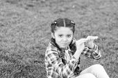 Kid Gadabout. Girl Little Kid Spend Leisure Outdoors In Park. Girl Sit On Grass In Park. Child Enjoy poster