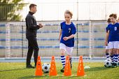 Young Happy Blonde Soccer Player Running With Ball On Training. Coach Of Youth Football Team Explain poster