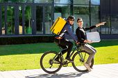 Male Courier With Thermal Bag Is Carrying A Guy With A Box On A Bicycle Trunk. A Man, Sitting On The poster