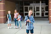 Handsome pre-adolescent teen boy student hanging out with friends after school. Selective focus on t poster