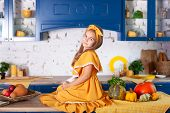 Smiling Little Girl Sitting On Work Surface Of Kitchen Waiting For Breakfast. Cheerful And Mischievo poster