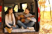 Young Couple With Guitar Sitting In Open Car Trunk Outdoors poster