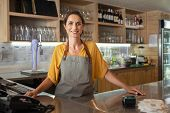 Mature woman barista standing behind the bar counter in coffee shop and looking at camera. Smiling s poster