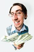 stock photo of holding money  - Photo of happy man holding packs of dollars in hands and looking at camera - JPG