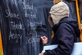 An Ecological Campaigner Is Seen As She Writes Words On A Blackboard To Describe Shame And Disgust A poster