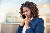 Frowning Concerned Manager Speaking On Cellphone Outside. Young African American Business Woman Stan poster