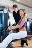 Young couple exercising in gym on different power machines to strengthen the muscles, the man is per