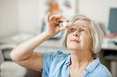 Senior Woman Dripping Some Medicine With Dropper On Her Eyes At The Ophthalmological Office. Concept poster
