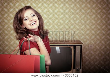 art portrait of young smiling woman and holding shopping sale bags in room with vintage wallpaper, retro stylization 60-70s, toned