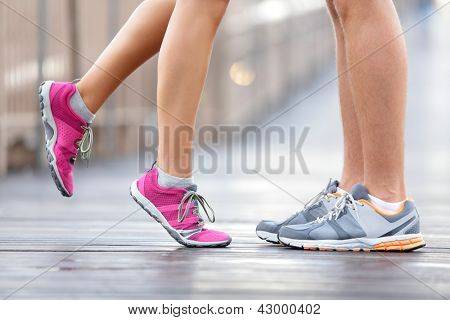 Love sport concept - running couple kissing. Closeup of running shoes and girl standing on toes to kiss boyfriend during jogging workout training outdoors on brooklyn bridge, New York City.