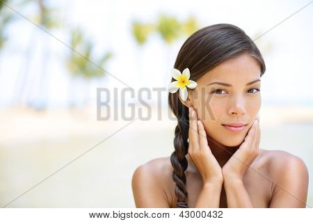 Wellness beauty portrait. Serene multicultural woman outdoors at tropical luxury spa resort. Young mixed race Asian Caucasian female model on Hawaii.