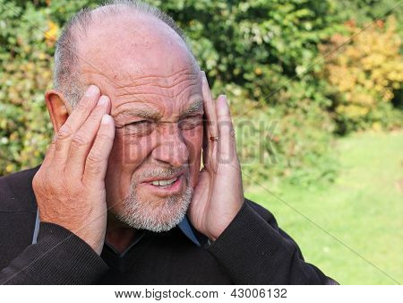 Old man with severe Migraine Headache holding hands to head
