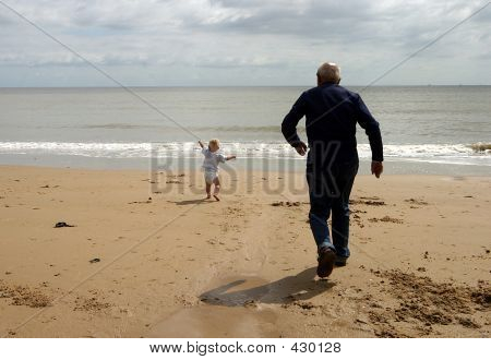 Little Boy And Grandfather Running For The Sea