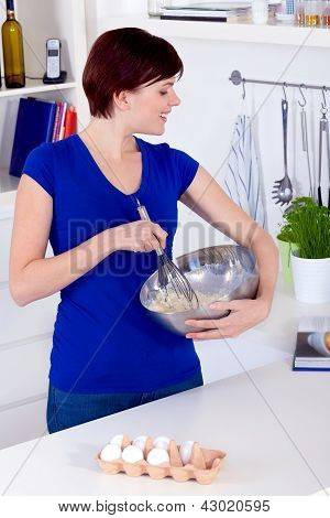Woman Preparing Dough For A Cake And Checking The Receipe