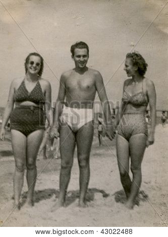 Vintage photo of man and two women in bathing suits on beach (thirties)