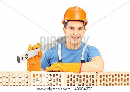 Male construction worker holding a bubble level and resting on a brick wall isolated on white background