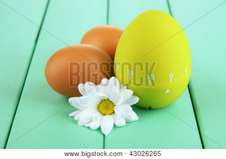 Green egg timer and eggs, on color  wooden background