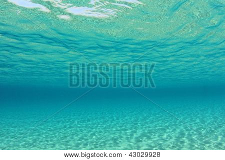 Background image of sunlight on ocean floor in clear blue water