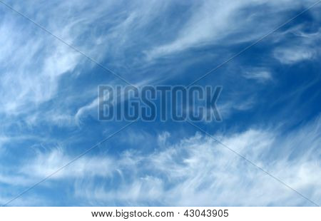 Blue sky background with wavy fleecy clouds