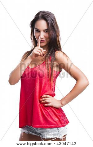 Beautiful young woman with finger in front of mouth, asking to make less noise, isolated over white