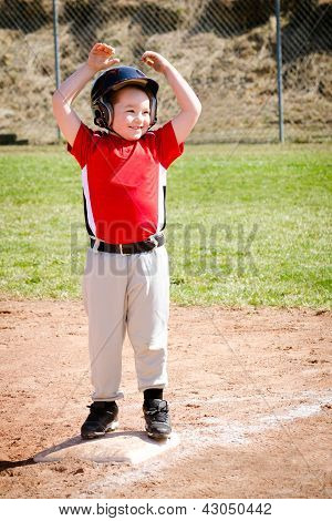 Child celebrates on base after making a hit during baseball game