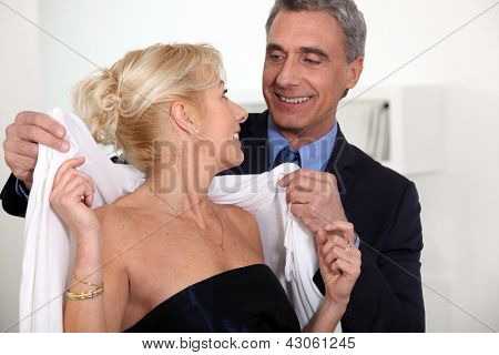 man placing scarf on woman
