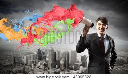 young businessman smiling in black suit holding megaphone