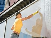 stock photo of window washing  - women in yellow T - JPG