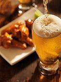 stock photo of alcoholic beverage  - pouring beer with chicken wings in background - JPG