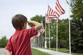 stock photo of salute  - A young boy salutes the flags of a Memorial Day display along a small town street - JPG