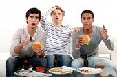 picture of threesome  - male trio watching soccer match on TV and eating hamburgers - JPG