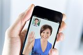 foto of video chat  - Closeup of a male hand holding an apple iphone during a video call with his girl field - JPG