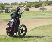 image of caddy  - Golf caddy trolley and bag on a golf course with bunker in the background - JPG