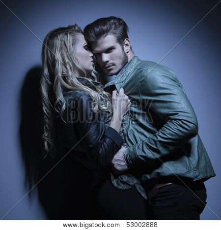 fashion couple in leather jackets pulling each other closer, man looking at the camera