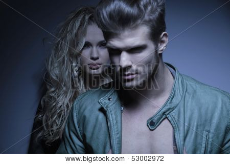 dramatic picture of a young fashion man standing in front oh his girlfriend and looking away, focus on the woman