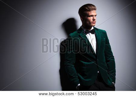 relaxed young fashion model in green velvet elegant suit with neck bow tie looking away from the camera white standing with his hands in pockets