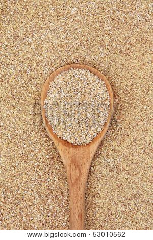 Wheatgerm in a wooden spoon forming a textured background.