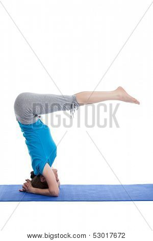 Yoga - young beautiful woman yoga instructor  doing Lowered Bound Headstand (Salamba sirsasana with Urdhva Dandasana) exercise  isolated on white background