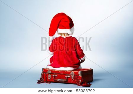 girl with Santa cap sitting on suitcase