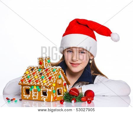 Girl in Santa's hat with gingerbread house