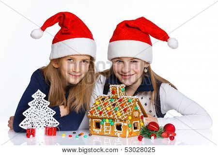 Girls in Santa's hat with gingerbread house