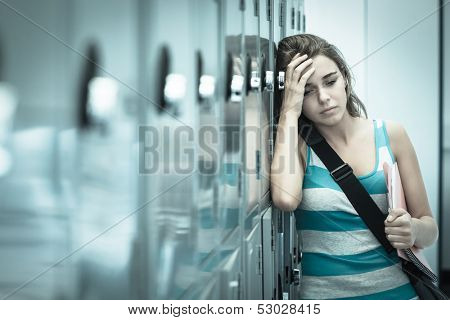 Wincing pretty student having a headache in school