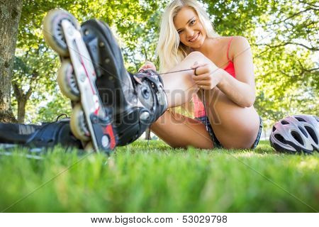Casual happy blonde tying shoelaces of roller blades in a park
