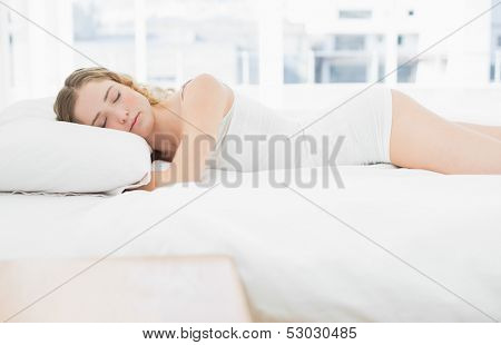 Pretty content blonde lying in bed slumbering in bright bedroom