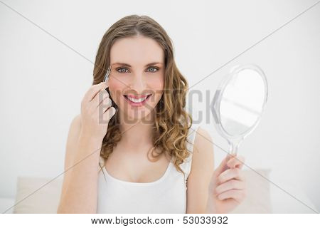 Pretty woman plucking her eyebrows while smiling into the camera and holding a mirror