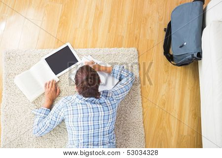 Young female student doing assignments while using her tablet and lying on the floor in the living room