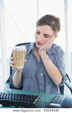Tired businesswoman holding a disposable cup sitting at her desk
