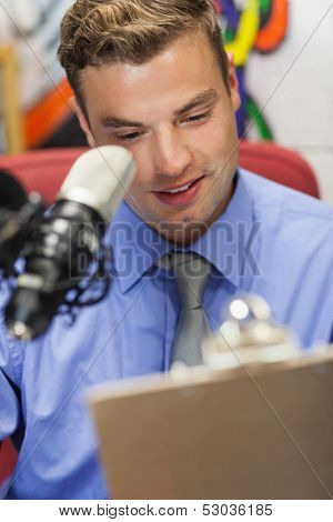 Well dressed smiling radio host moderating holding clipboard in studio at college