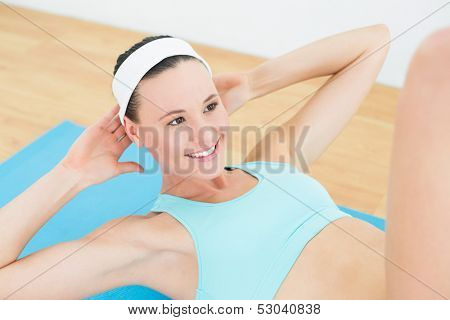 Sporty fit smiling woman doing sit ups on exercise mat in fitness studio
